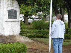 08 Mary reading inscription in Plaza de Armas, Puerto Aisen