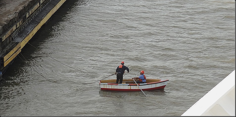 Men in rowboat waiting for mooring rope from Prinsendam